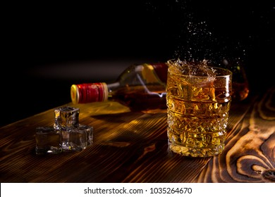 a bottle of whiskey on a wooden dark background, a glass of whiskey and ice spray