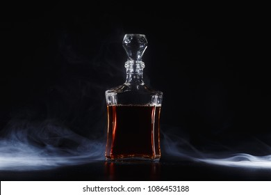 a bottle of whiskey,  or rum, or alcohol stands on a table on a dark background