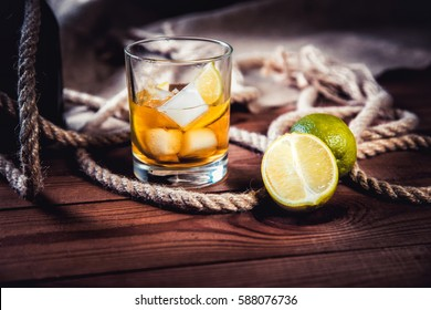 A bottle of whiskey, rum, brandy, lime on a wooden background