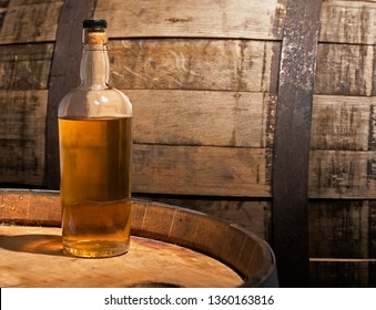 Bottle of whiskey sitting on a barrel