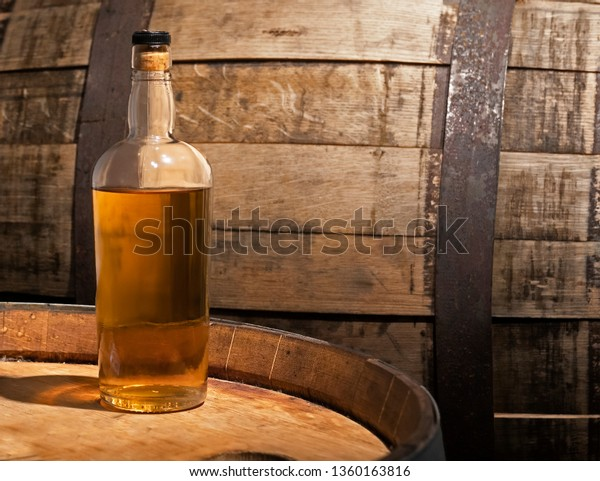 Bottle of whiskey sitting on a barrel
