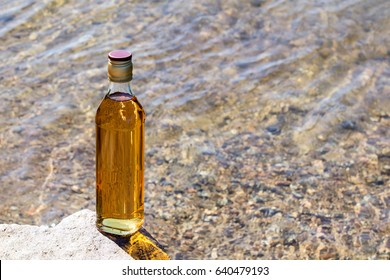 Bottle of whiskey stands on a stone in a mountain river