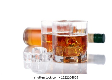 Bottle of whisky and two glasses of whisky with ices on a white background with reflection