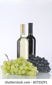 A bottle of white and red wine with grapes