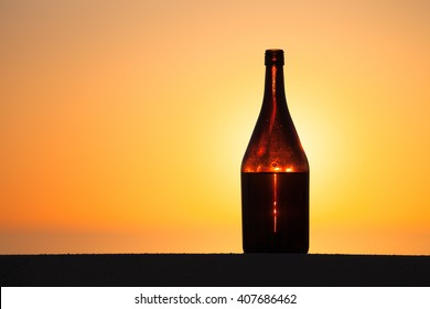 Bottle of white vine with reflections of houses and view to beautiful sunset. Selective focus.