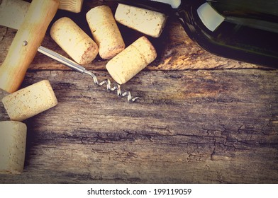 Bottle of white wine, corkscrew and corks on wooden table. Background