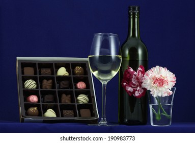 A bottle of White Wine, a glass of White Wine, a couple of Carnation flowers and a box of confectionery Chocolate against a blue background