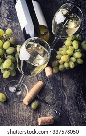 Bottle of white wine, glass, grape and corks on old wooden background