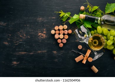 A bottle of white wine with glasses and grapes. Leaves of grapes. Top view. On a black wooden background. Free space for text.