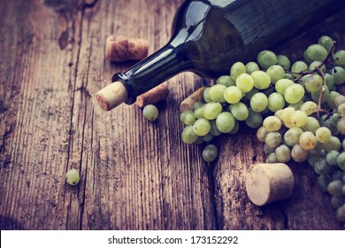 Bottle of white wine, grape and corks on wooden table