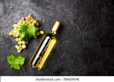 Bottle of white wine with grapes and leaves on dark concrete background.