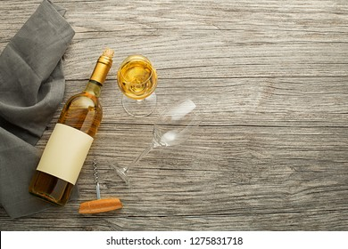 Bottle of white wine with label on old board. Glass of wine and cork. Wine bottle mockup. Top view
