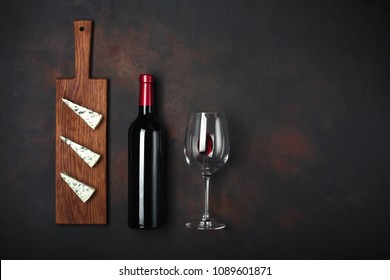 Bottle of wine, blue stinky cheese and wineglass on rusty background, up wiev