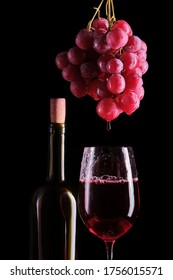 A bottle of wine and a bunch of red grapes, with which red wine drips into a glass.