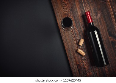 Bottle of wine corks and wineglass on rusty background up wiev