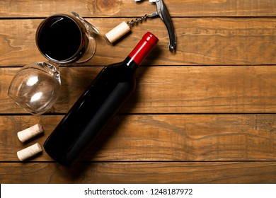 Bottle of wine corkscrew and corkscrew on wooden background. Top view with copy space.