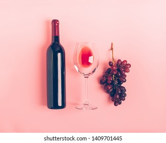 A bottle of wine an empty glass of a bunch of red grapes on a gentle pink background. Flat layout top view. Copy space. Minimalism. Horizontal frame
