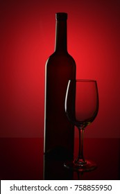 Bottle of wine and empty wine glass on red background