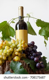 Bottle wine of fresh white and red grape on wooden table