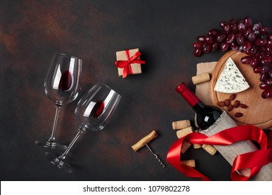 Bottle of wine, gift box, red grapes, blue cheese, almonds, corkscrew, rope and corks, on rusty background top view