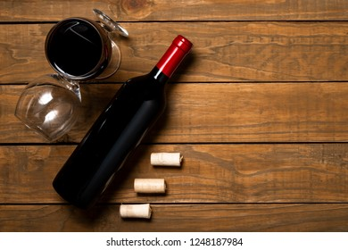 Bottle of wine glass and corks on wooden background. Top view with copy space.