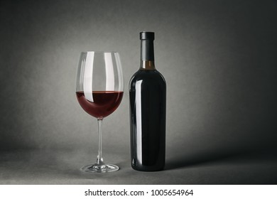 Bottle of wine and glass on gray background