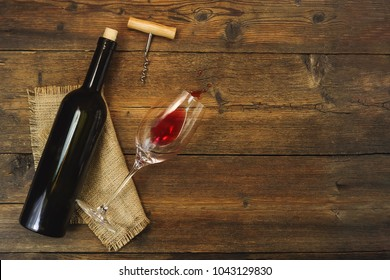 a bottle of wine and a wine glass on a wooden background