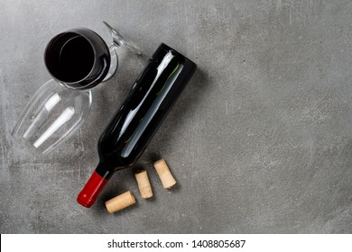Bottle of wine glasses and corks on concrete background. Copy Space.