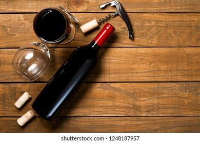 Bottle of wine glasses corkscrew and corkscrew on wooden background. Top view with copy space.