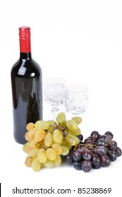 Bottle of wine with glasses and grapes isolated in white