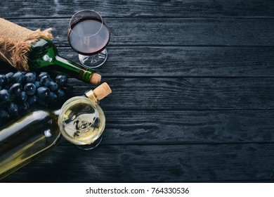 A bottle of wine with glasses and grapes on a black wooden background. Free space for text. Top view.