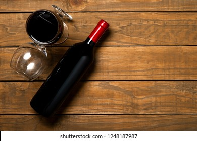 Bottle of wine and glasses on wooden background. Top view with copy space.