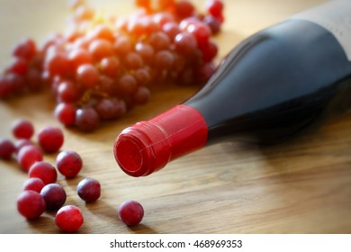 Bottle of wine and grape on wooden background