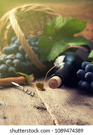 bottle of wine and grapes in basket on old wooden background. toning