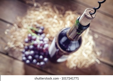 Bottle of wine, grapes, cork and corkscrew on wooden table