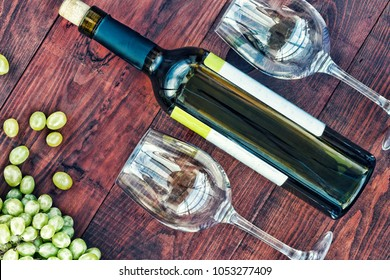 bottle of wine, grapes and glasses on a wooden dark background. Concept: wine, winemaking