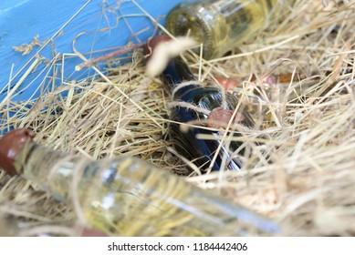 A bottle of wine with a heart icon lies in the hay, close-up