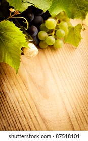 bottle of wine with leaves and grapes on wooden table