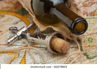 bottle of wine and old corkscrew on the background of old maps