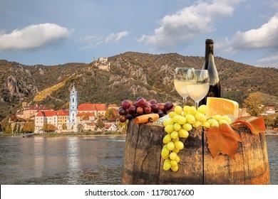 Bottle of wine on barrel with Durnstein village in Wachau, Austria