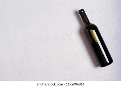 Bottle of wine on white stone texture background. View from above, top studio shot