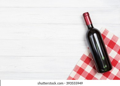 bottle of wine on the white table with the red napkin.