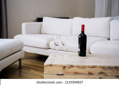 Bottle of Wine on wooden table in empty room with white sofa.