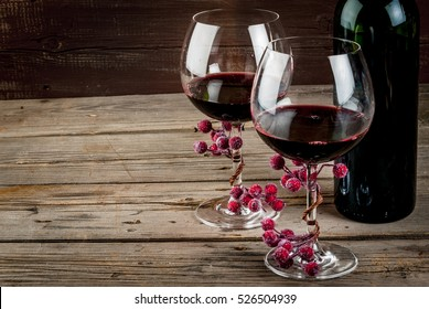 Bottle of wine and two glasses of wine, decorated with artificial branch of winter berries. The festive mood, Valentine's Day, Thanksgiving or Christmas. Copy space.
