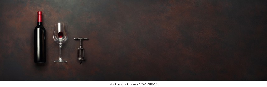 Bottle of wine with wineglass and corkscrew on rusty brown background. Panoramic top view with copy space for your text.