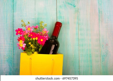 a bottle of wine in a yellow package as a gift, next flowers, gifts, copy space, on blue wooden background, to give girls a set of gentlemen for Dating