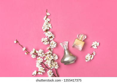 Bottle of woman perfume and branch of spring apricot cherry white flowers on bright pink background. Beauty, Perfumery, cosmetics. Spring minimal concept. Flat lay top view copy space.