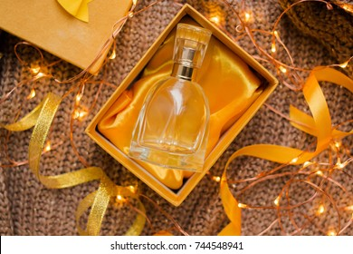 bottle of woman perfume on knitted background with yellow and gold ribbons. gift. yellow packeging of present present with garland