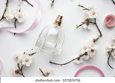 bottle of woman perfume on white background with spring apricot and cherry flowefs. gift. pink ribbon