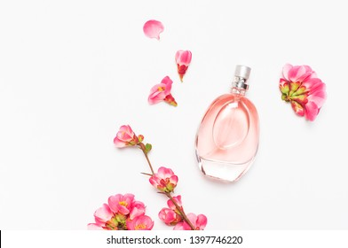 Bottle of women's perfume with pink spring flowers on light gray background top view flat lay copy space. Perfumery, cosmetics, female accessories, fragrance collection. Delicate Pink Perfume Bottle